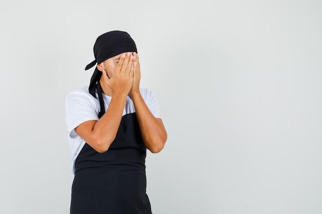 Uomo panettiere in t-shirt, grembiule che copre il viso con le mani e sembra depresso
