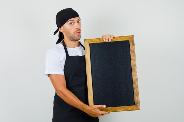 Baker man in t-shirt, apron holding blackboard and looking puzzled