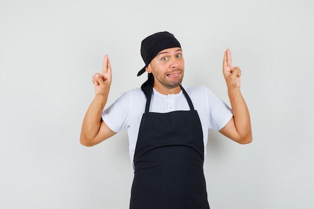 Uomo panettiere in maglietta, grembiule tenendo le dita incrociate e guardando confuso