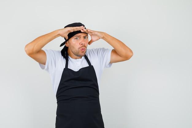 Uomo del panettiere in maglietta, grembiule che guarda lontano con le mani sopra la testa