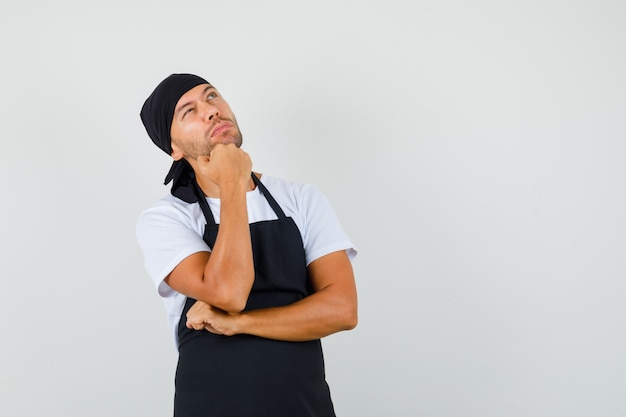 Uomo panettiere in t-shirt, grembiule che osserva in su con il mento appoggiato sulla mano e che sembra pensieroso
