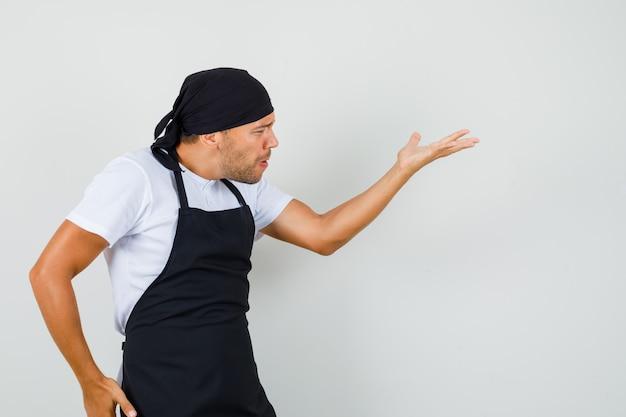 Uomo del panettiere in maglietta, grembiule che fa gesto di domanda e che sembra arrabbiato