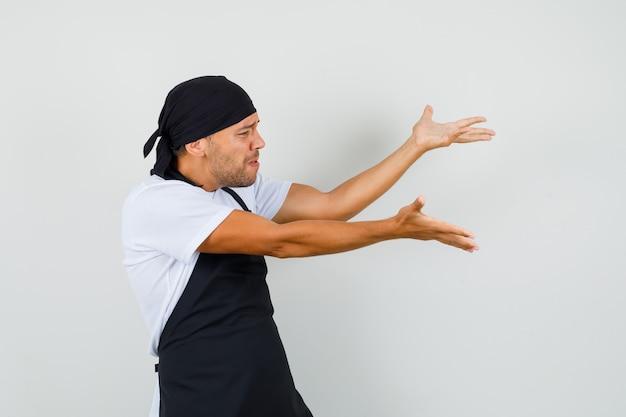 Uomo del panettiere in maglietta, grembiule che fa gesto di domanda e che sembra nervoso