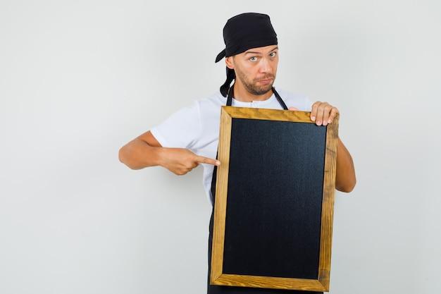 Uomo del panettiere in maglietta, grembiule che punta alla lavagna