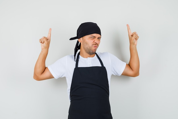 Uomo panettiere in maglietta, grembiule che punta le dita verso l'alto e accigliato