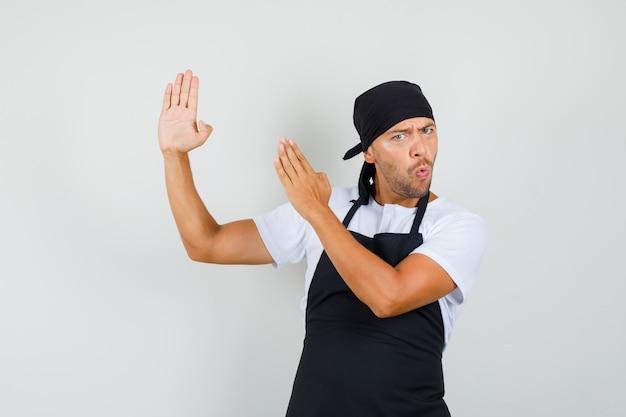 Uomo del panettiere in maglietta, grembiule che mostra il gesto di taglio di karate e che sembra fiducioso