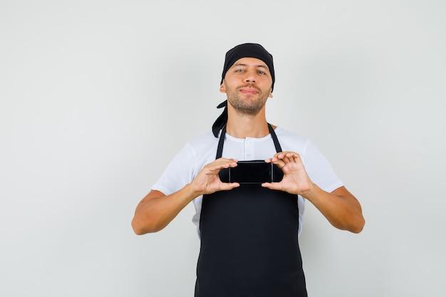 Tシャツで携帯電話で写真を撮るベイカー男