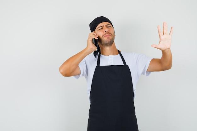 携帯電話で話しているベイカーの男、tシャツで停止ジェスチャーを示しています