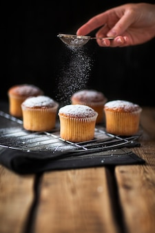 Baker pouring powdered sugar over muffins
