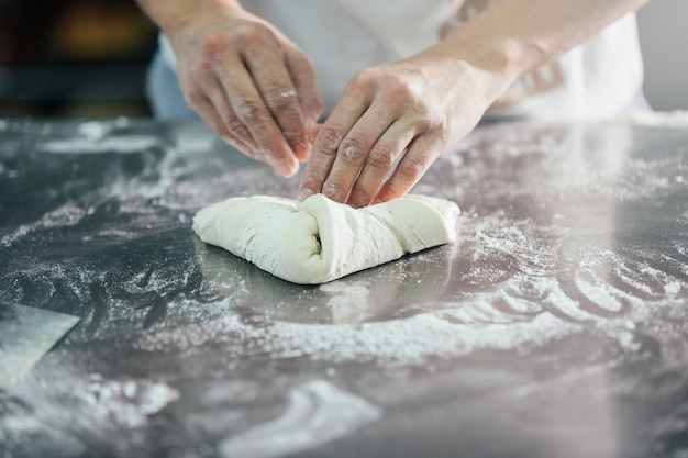 Baker preparing bread. close up of hands kneading dough. bakery concept.