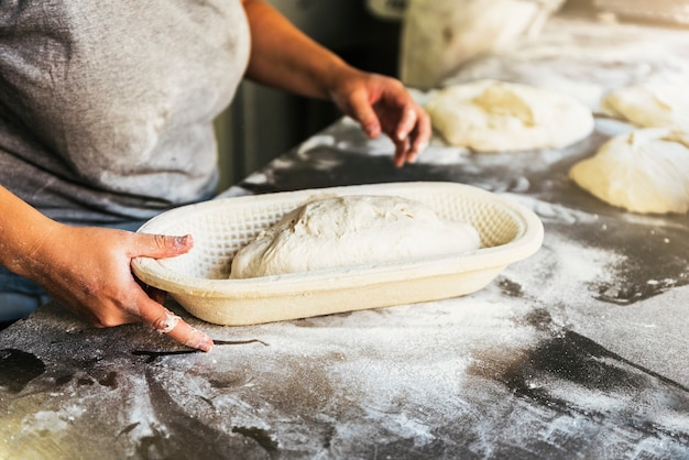 パンを準備するベイカー。生地をこねる手のクローズアップ。ベーカリーのコンセプト。