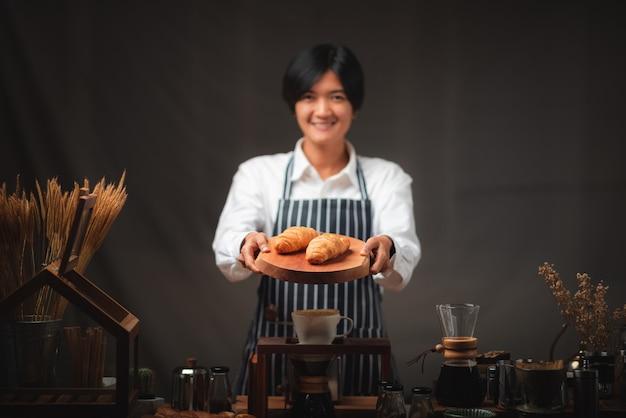 Baker presenting freshly baked croissants in cafe
