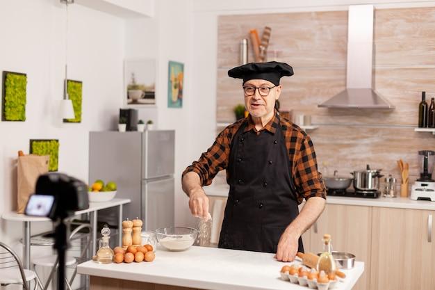 Пекарь представляет, как использовать пшеничную муку во время записи видеоурока. блогер-пекарь на пенсии, влиятельный человек, использующий интернет-технологии для общения, съемки и ведения блога в социальных сетях с помощью цифрового оборудования.