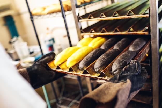 ベイカーは、ホットドッグ用の黄色と黒のパンが入ったラックベーキングシートを入れます。