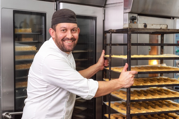 Baker putting a rack of pastries into the oven in bakery or pastry shop.
