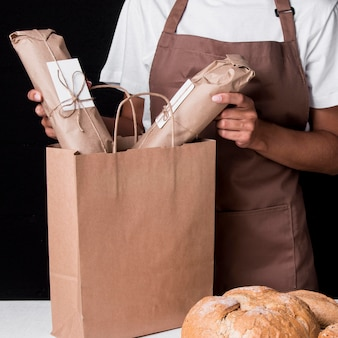 Baker mettendo il pane avvolto in un sacchetto di carta