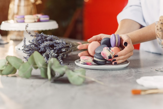 Baker's female hands pour colored macarons into a white plate on a marble table.