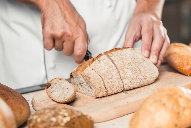 Baker's hand cutting fresh bread with knife