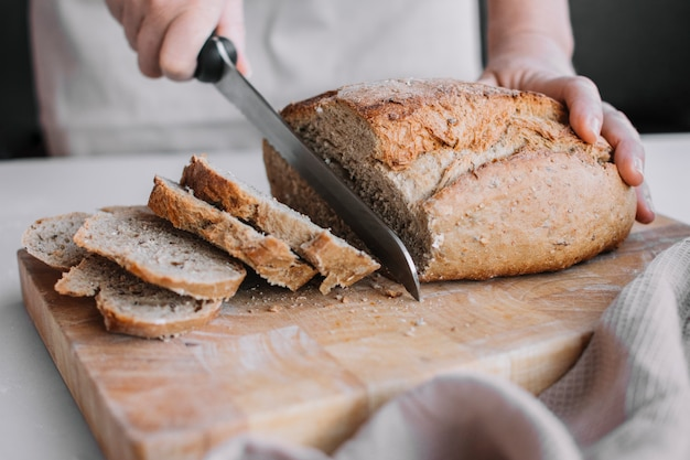 Baker's hand slicing loaf of fresh bread with knife