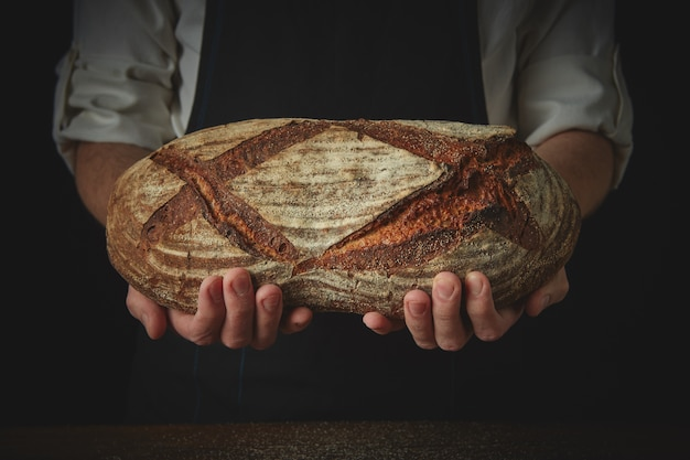 베이커의 손에 검은 앞치마에 신선한 타원형 빵을 들고