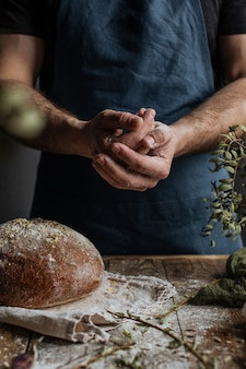 The baker's hands hold a loaf of rye bread over a wooden table.