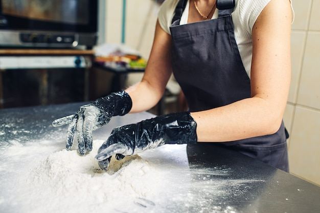 Руки пекаря в черных перчатках замешивают тесто.