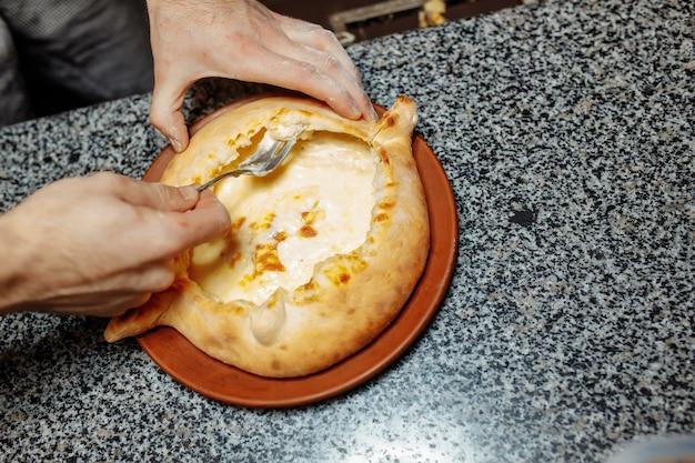 台所のテーブルでハチャプリを準備するベイカーの手