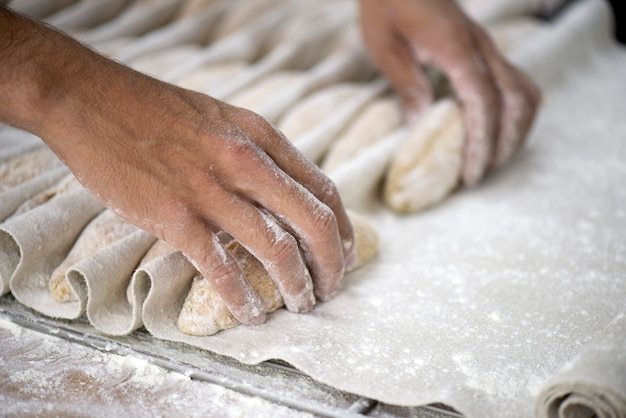 The baker shapes the bread to be baked