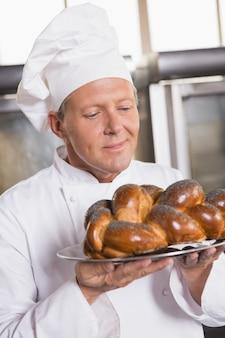 Baker showing freshly baked loaf