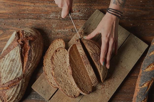 Бейкер нарезает хлеб с отрубями на разделочной доске плоская планировка