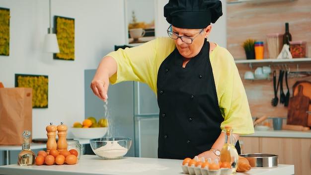 Пекарь выкладывает муку на деревянный стол у себя дома в современной кухне в фартуке и косточке. счастливый пожилой повар с равномерным посыпанием, просеиванием, просеиванием сырых ингредиентов вручную, выпечкой домашней пиццы