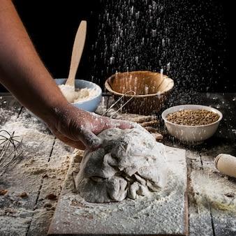 Baker sprinkling the flour on the dough