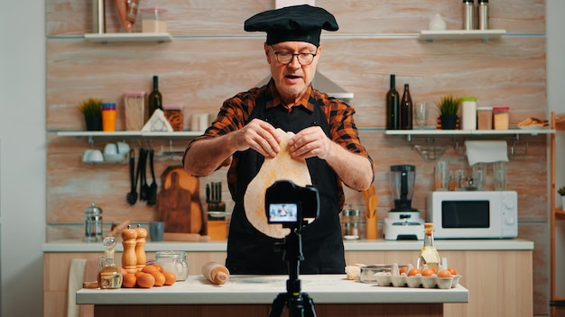 Baker using wooden rolling pin for dough in front video camera recording new cooking episode. old blogger chef influencer using internet technology communicating on social media with digital equipment