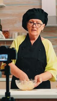 小麦粉とひびの入った卵を使った伝統的な料理レシピのボーンテレコーディングポッドキャストを身に着けているベイカー。インターネット技術を使用したインフルエンサーシェフのコミュニケーション、デジタル機器を使用したソーシャルメディアでの撮影
