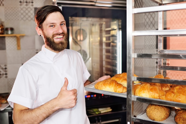Baker in white uniform holding in his hands a tray full of freshly baked croissants