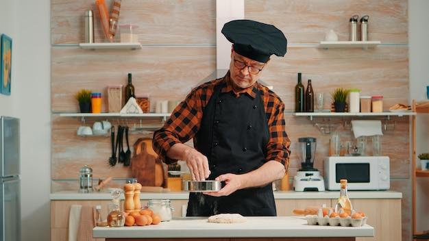 家庭でベーカリー製品を準備する金属ふるいを使用して、骨とエプロンを使ったパン屋。キッチンの制服を着て、伝統的なパンを焼くために原材料を混ぜ、振りかけ、ふるいにかける幸せな年配のシェフ
