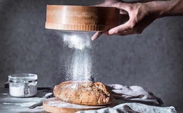 彼の手で小麦粉とパン屋