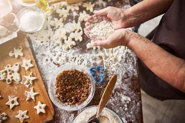 Baker with handful of flour near kitchen table