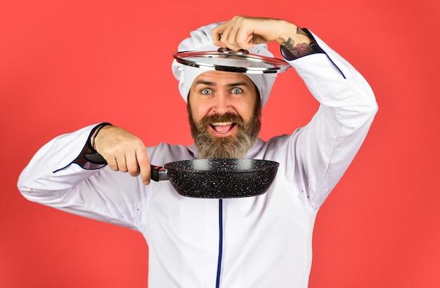 Пекарь с кастрюлей. общественное питание. мужчина шеф-повара держит посуду. счастливый повар мужчина держит сковороду. шеф-повар в мундире готовит суп. кухня ресторана. готовить обед на кухне. моя профессия.