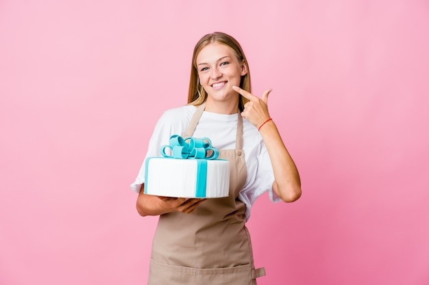 Baker woman holding a delicious cake smiles