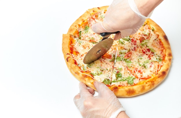 Руки пекаря разрезают пиццу на кусочки на изолированном белом
