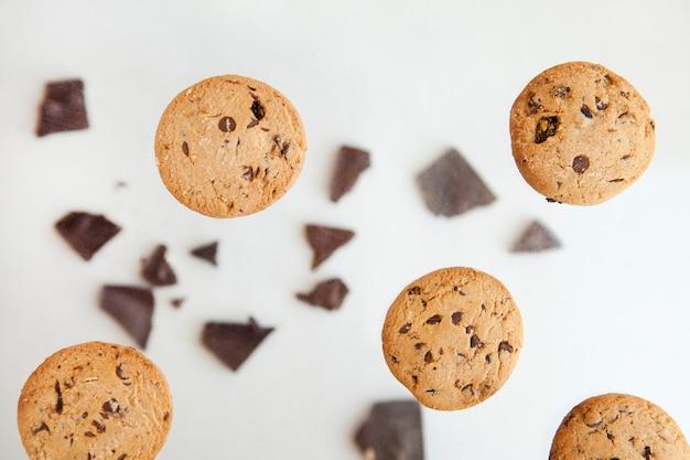 회색 배경에 부스러기가 있는 초콜릿 칩 쿠키를 날리는 베이커리 및 디저트 초콜릿 쿠키