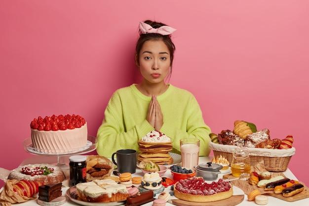 Выпечка и сладкая еда. умоляющая кореянка сжимает ладони вместе, просит разрешения съесть еще один кусок торта