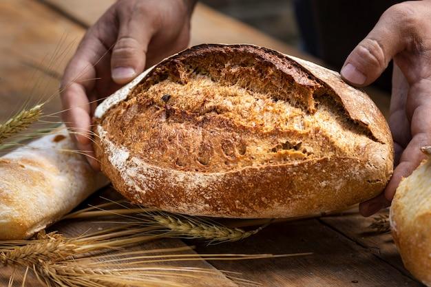 パン屋の背景。パン屋の手にある焼きたてのカリカリのパンがクローズアップ