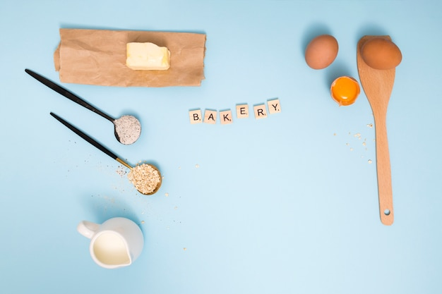 Bakery blocks with butter; milk pitcher; oats barn; flour; eggs and wooden spatula on blue background
