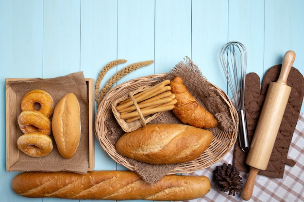Bakery bread on blue wooden table. various bread and sheaf of wheat ears.