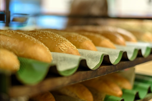Bakery, bread.fresh buns with sesame on tray rack from side view.