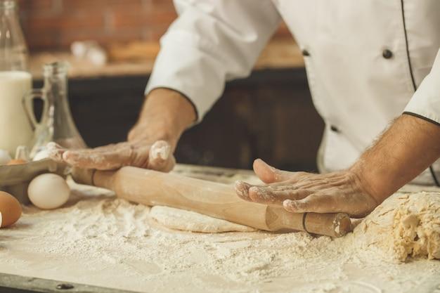 キッチンのプロのロールアウト生地で焼くベーカリーシェフ