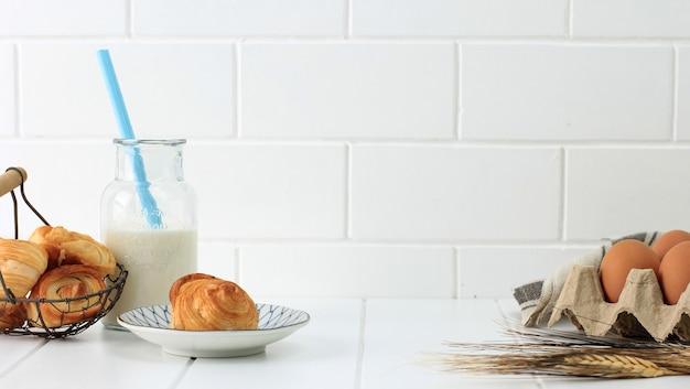 베이커리 컨셉 화이트, 미니 크루아상, 계란, 우유 한 병. 광고/텍스트 복사 공간