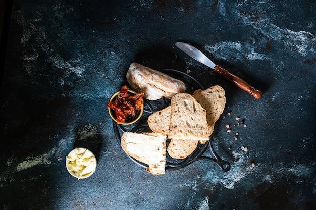 ベーカリー、無愛想なパンの塊。上から見た静物、フラット横たわっていた。天日干しトマト。ベジタリアンフード。健康食品のコンセプトです。バター。サンドイッチ。サワードウで作ったパン。